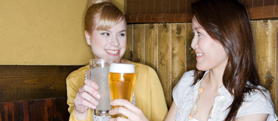 women at a bar drinking water and beer